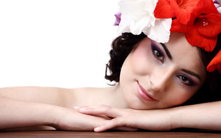 Beautiful young woman with flowers in their hair looks at the camera photo