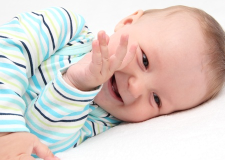 lying on back: little baby laughing Stock Photo