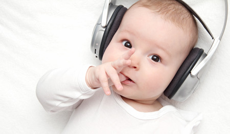 listening back: baby boy with headphone lies on back Stock Photo