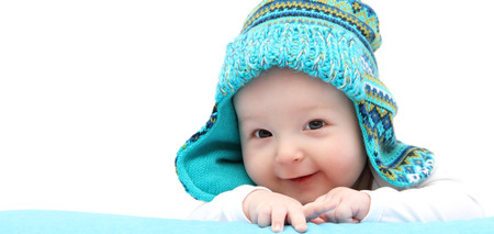 happy baby boy in knitted hat on stomach