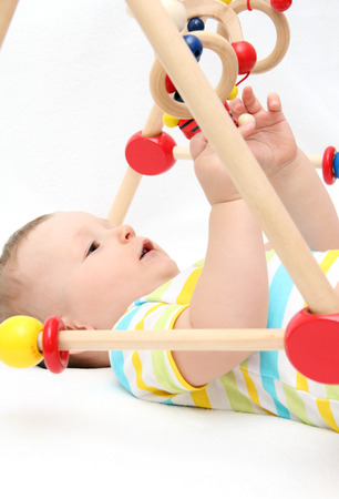Beautiful baby on back playing with toys