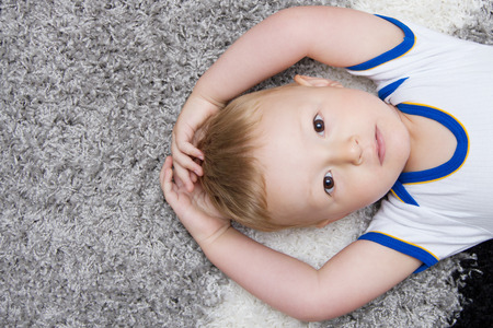 emotionless: cute baby lying on back Stock Photo