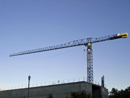Enormous construction crane at work lifting materials on construction site against blue sky