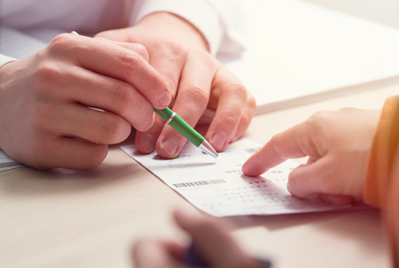 orthography: In the foreground the hand holding the pen Indicates bill Stock Photo