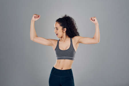 Cropped studio shot of an attractive young sportswoman flexing her biceps while standing against a grey background