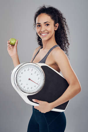 Cropped studio portrait of an attractive young sportswoman holding an apple and a weight scale against a grey background Stock Photo