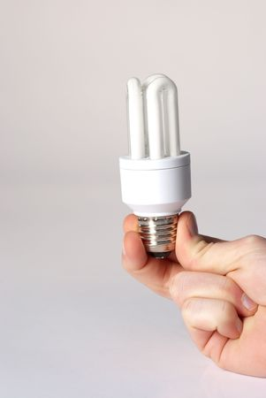 A hand holding a low energy lamp isolated against i white background photo