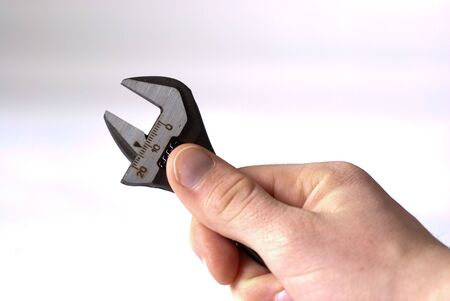 crescent wrench: A hand holdning an adjustable spanner isolated on a white background