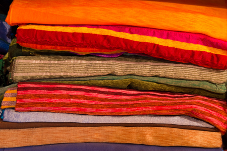 carpets, scarfs and blankets piled in a moroccan textile shop
