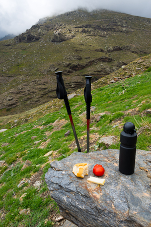 hiking sticks with lunch and backpack at mountain range in sierra nevada, spain Stock Photo