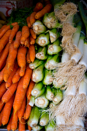 stacks of carrots, leek and chard on market stall in cadiz, spain