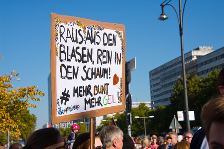 signs and crowd of activists at huge #unteilbar demonstration in berlin, germany  placard translation: out of the bubbles, into the foam  more colorful, more cool Redakční
