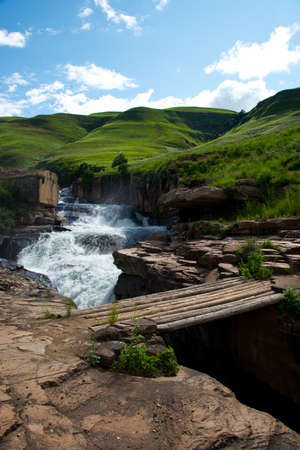 wooden footbridge over  rapids of mnweni river, northern drakensberg mountains, kwazulu natal, south africa 版權商用圖片