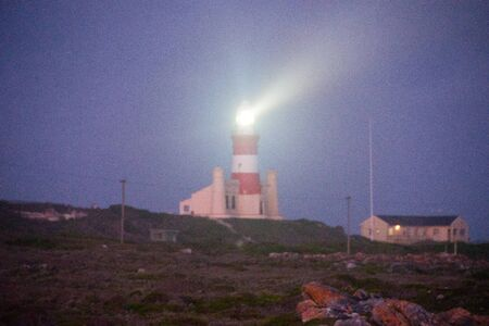 night view of lighthouse and beacon at cape agulhas, southernmost point of africa, where atlantic and indian oceans meet