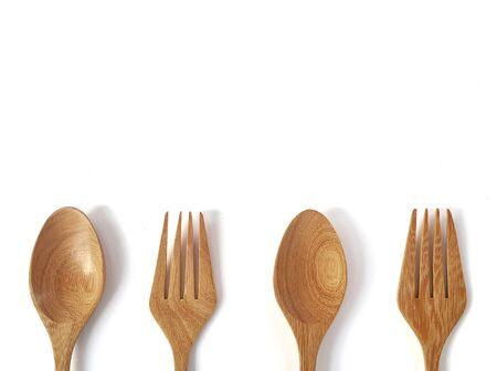 Cucchiai e forchette in legno su sfondo bianco