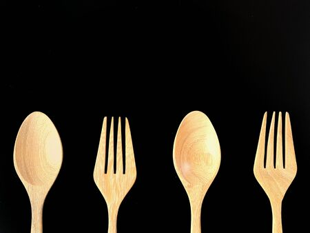 materia: Spoons and forks made of wood on black background