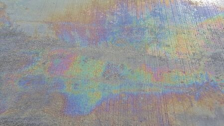 smutty: Oily Rainbow stains on the cement road.