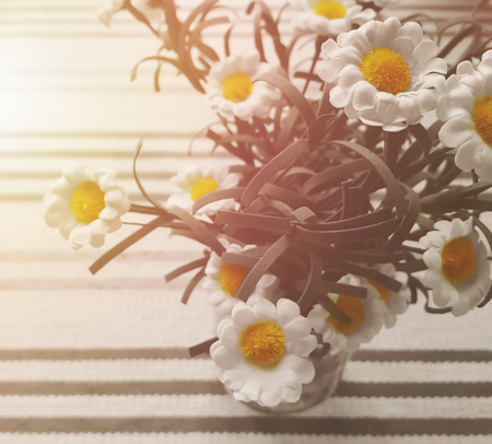 Daisy flower on tablecloth with sunlight.vintage tone,copy space,card