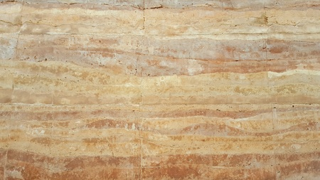 Textures and design by nature of a rammed earth wall.Cracks in the wall. Nature orange background.wallpaper,copy space