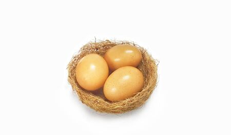 Three eggs in bird's nest isolated on white background. Nutritional value Stock Photo - 98777489
