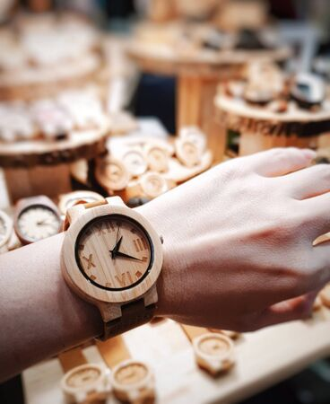 The round shape watch shows Roman numerals made from wood, worn on the wrist of women at 13.21 minutes Reklamní fotografie