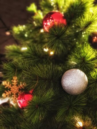 christmas ball on tree.Christmas tree decorated with beautiful ornaments and lighting. garland background and xmas wallpaper Фото со стока