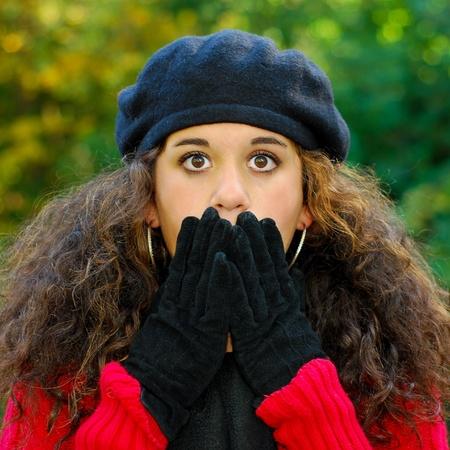 occhi sbarrati: Ragazza sorpresa o paura che copre la bocca con le mani, gli occhi spalancata