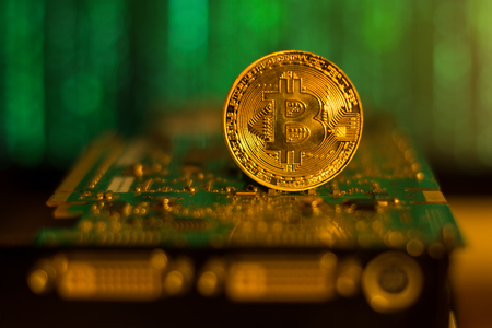 Bitcoin closeup on a mining graphic card with matrix background Stock Photo