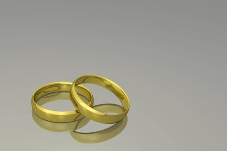 Gold wedding bands on a grey background.