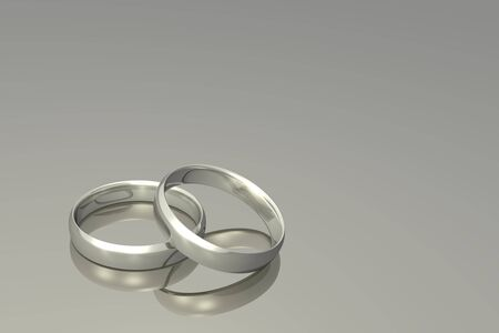 silver background: Silver wedding bands on a grey background.
