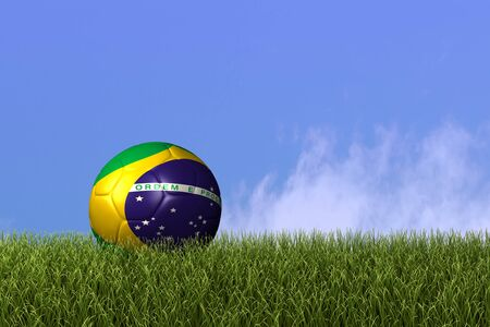Image of a soccer ball with the flag from Brazil on grass. photo