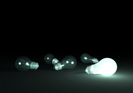 Lit bulb next to unlit light bulbs.