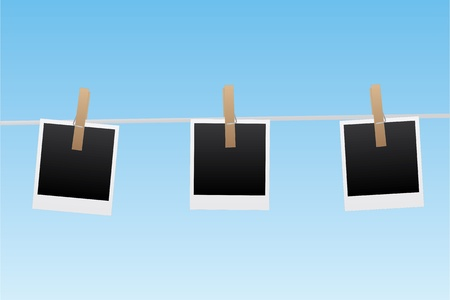 hung: Image of pictures hanging on a line with a blue sky background.