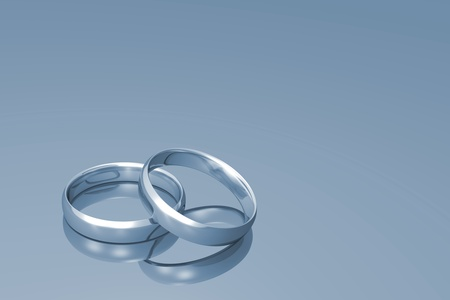Silver wedding bands on a grey background.