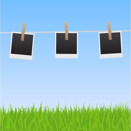 hung: Image of pictures hanging on a clothes line with a sky and grass background.
