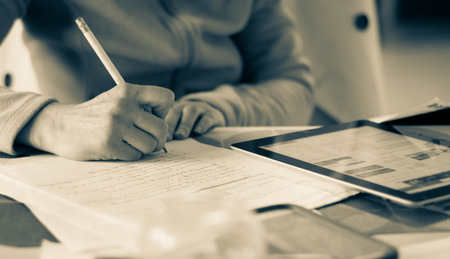 person writing: Illustration of a woman taking notes or writing a letter.