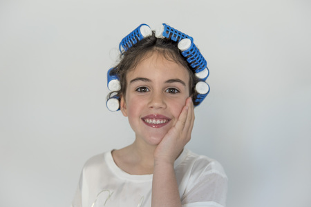 little girl posing with curlers, amazed at how her hair looks