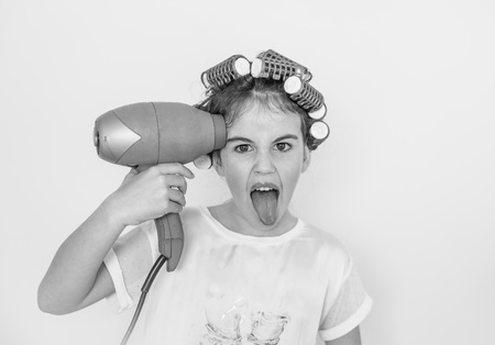 little girl posing with curlers and hair dryer, amazed and happy