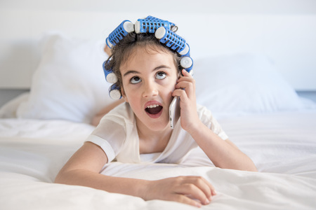 little girl posing with curlers and Smartphone, surprised and happy Stock Photo