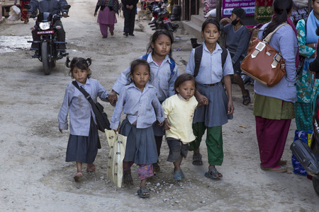 come home: PANAUTI, NEPAL - DECEMBER 2, 2013  five poor children come home after school with the modest and dirty uniform of the public school on december 2, 2013 in Panauti  Panauti is a historical city in Nepal, 36 km South-East from the capital city Kathmandu