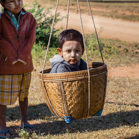transported: BAGAN, MYANMAR - NOVEMBER 26, 2014: an unidentified Burmese child is  transported by the mother in a basket in the fields among the ancient temples of Bagan