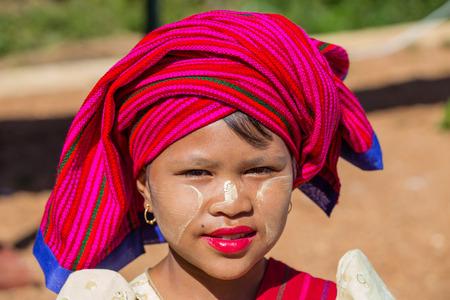 thanaka: INLE LAKE, MYANMAR - November 30, 2014: an unidentified girl in traditional dress sells textiles crafts at the market of Inn Dain Khone Village on Lake Inle. On the face the girl has the traditional Burmese makeup (thanaka).
