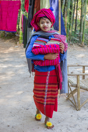 INLE LAKE, MYANMAR - November 30, 2014: an unidentified girl in traditional dress sells textiles crafts at the market of Inn Dain Khone Village on Lake Inle. On the face the girl has the traditional Burmese makeup (thanaka).