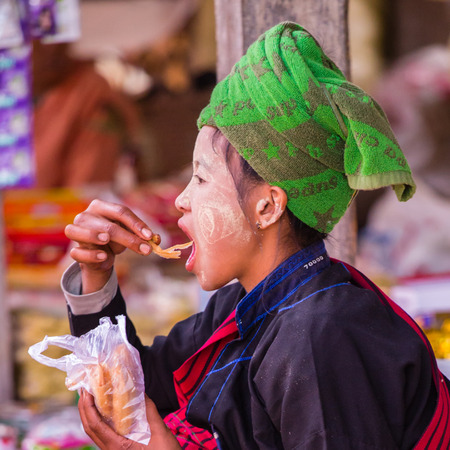 thanaka: INLE LAKE, MYANMAR - December 01, 2014: an unidentified girl in traditional dress has a snack at market of Inn Dain Khone Village, on Inle Lake. On the face the traditional makeup thanaka Editorial