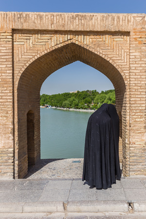 isfahan: ISFAHAN IRAN APRIL 28 2015: unidentified woman resting in the ancient bridge SioSeh Pol The Bridge of 33 Arches in Isfahan Iran