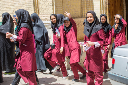 jilbab: SHIRAZ, IRAN - APRIL 26, 2015: unidentified young female students out of school in uniform, in Shiraz, Iran