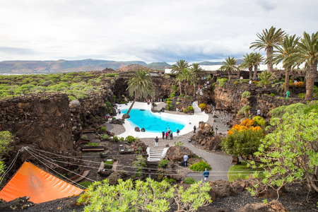 conceived: LANZAROTE, SPAIN - NOVEMBER 29, 2016: people at the Jameos del Agua, part of a 6Km long lava tube which formed about 4,000 years ago when the Montana La Corona erupted. The tourist attraction was conceived by Cesar Manrique, during the 1960s in Lanzarote Editorial