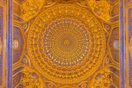 registan: SAMARKAND, UZBEKISTAN - AUGUST 28, 2016: Detail of gold mosaic dome in Tilya Kori Madrasah in Samarkand, Uzbekistan