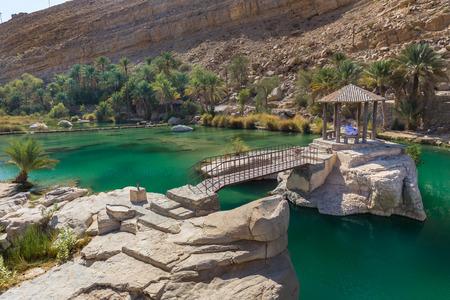 WADI BANI KHALID, OMAN - NOVEMBER 26, 2017:  A man relaxes at the amazing view of the emerald pools in Wadi Bani Khalid, Oman