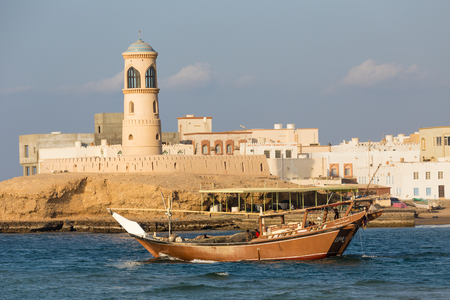 SUR, OMAN - NOVEMBER 25, 2017: Lighthouse and traditional boat in the bay of Sur, Oman Editorial